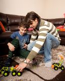 Brothers playing with plastic trucks Stock Photos