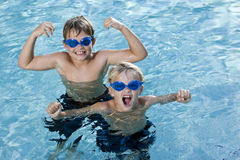 Brothers playing and shouting in swimming pool. Boys, 7 and 9 years, smiling and shouting in swimming pool Royalty Free Stock Photo