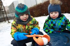 Brothers playing with snowball maker Stock Photo