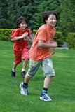 Brothers playing tag at the park. Two multi ethnic brothers play tag in the park Stock Images