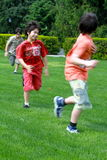 Brothers playing tag at the park. Two multi ethnic brothers play tag in the park Stock Photos