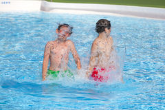 Brothers playing together in the pool. Cute boys playing together in the pool Royalty Free Stock Photo