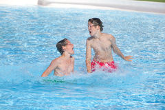 Brothers playing together in the pool Royalty Free Stock Photos