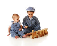 Brothers Playing Train. Young brothers in striped denim work clothes and an engineer's cap playing with a wooden toy train.  Isolated on white Stock Image
