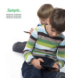 Brothers playing video games on tablets Royalty Free Stock Photography