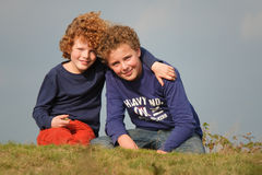 Brothers. Portrait of two happy brothers on a sunny autumn afternoon. Only sky as background Stock Image