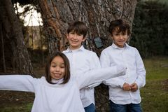 Brothers posing next to a tree stock image