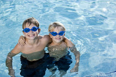 Brothers posing together in swimming pool. Boys, 7 and 9 years, in pool wearing swim goggles, smiling Stock Photos