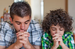 Brothers praying at home. Two Hispanic brothers praying and having their daily Christian devotional at home. Young children religious life. Religious lifestyle Royalty Free Stock Photography