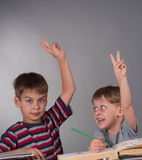 Brothers raising their hands to give an answer, education concept Stock Photos