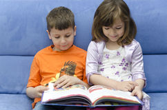 Brothers reading a book. A boy and a girl reading a book on a blue sofa Stock Photography