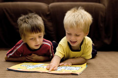 Brothers reading together. Brothers reading a book together Royalty Free Stock Image