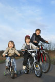 Brothers ride bikes Royalty Free Stock Image
