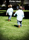 Brothers Running. Two young, identically-dressed brothers running in a park. High-key style Stock Photo