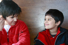 Brothers Sharing. Teenager and little brother share a moment with music. Both have one ear phone and they are looking lovingly at each other Royalty Free Stock Photo