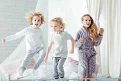 Brothers and sister on bed. Small brothers and sister jumping on bed Stock Photography