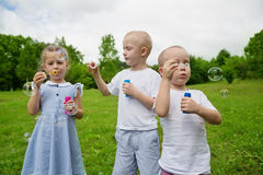 Brothers and sister blowing soap bubbles Royalty Free Stock Photo