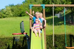 Brothers and sister playing on slide in the garden royalty free stock photos