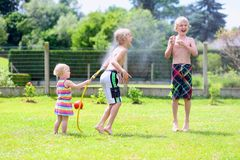 Brothers and sister playing with water hose in the garden Royalty Free Stock Photos