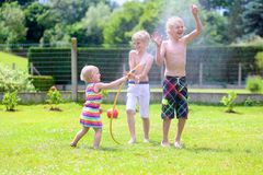 Brothers and sister playing with water hose in the garden. Happy laughing children, two young school boys and adorable toddler girl, enjoying hot sunny summer stock photography