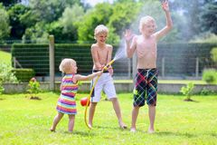 Brothers and sister playing with water hose in the garden. Happy laughing children, two young school boys and adorable toddler girl, enjoying hot sunny summer royalty free stock photos