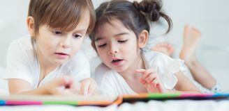 Brothers and sister read a bedtime story togather on the bed in Stock Image