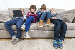 Brothers And Sister Using Technologies On Sofa Stock Images