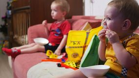 The brothers sit on the sofa at home and watch TV. Eat corn sticks and smile.  stock video