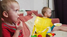 The brothers sit on the sofa at home and watch TV. Eat corn sticks and smile.  stock footage
