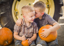 Two Boys Sitting Against Tractor Tire Holding Pumpkins Whispering Secrets royalty free stock image