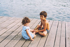 Brothers sitting on dock. Brothers sitting on wooden dock at waterfront Royalty Free Stock Photo
