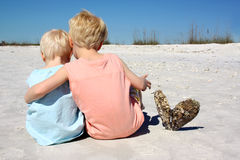 Brothers Sitting Together on Beach. A young child and his baby brother are sitting together with their arms lovingly around eachother at the beach, with their stock photography