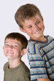 Brothers smiling. Big and little brother standing back to back smiling on a white background Stock Photos