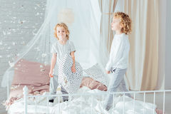 Brothers standing on bed. Cute, small brothers standing on bed, doing mess Stock Image