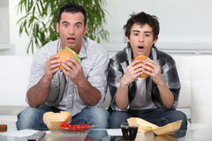 Brothers eating hamburgers. Brothers staring in amazement while eating a hamburger stock photography