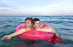 Brothers in a swim ring have fun in the ocean Stock Photography