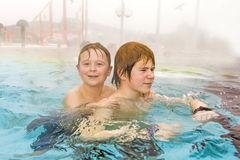 Brothers are swimming in the outside area of a thermic pool in W Stock Photo