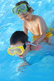 Brothers in swimming pool. An older brother gives younger brother a back ride in swimming pool Royalty Free Stock Photos