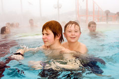 Brothers are swimming in the thermal pool. Brothers are swimming in the outside aarea of a thermic pool in Wintertime in warm water, it is foggy Stock Photography