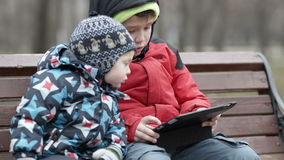 Brothers with tablet computer. Young boy watching his brother as the two sit together on a wooden park bench in warm winter clothing with the older child using a stock video footage
