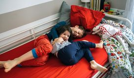 Brothers tickling and laughing lying on the bed. Brother and sister tickling and laughing while lying on the bed Royalty Free Stock Image
