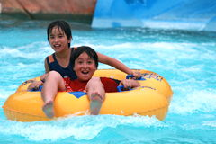 Brothers tubing in a water park. Asian brothers dare tubing on a fast and challenging slide on a summer day in a water park Stock Images
