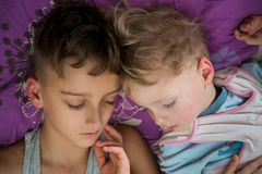 Brothers two boys sleeping together in bed Stock Images