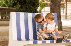 Brothers. Two little brothers hugging and playing on bench Stock Photography