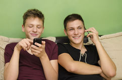 Brothers using smart phones Stock Photo