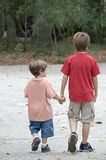 Brothers walking. Two brothers holding hands and walking Royalty Free Stock Photo