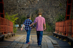 Brothers walking on a bridge. Stock Photo