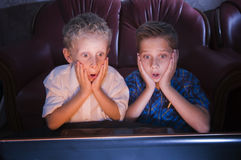Brothers watching scary TV. Frontal view of two brothers at the age of 7 and 13 years in the darkened room shocked looking at the TV royalty free stock photos
