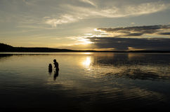 Brothers in the water of a big lake at sunset Stock Images