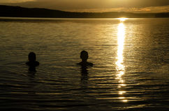 Brothers  in the water of a lake at sunset Royalty Free Stock Photo